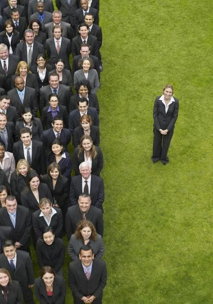 Business woman standing next to large group of business people in formation, elevated view, portrait